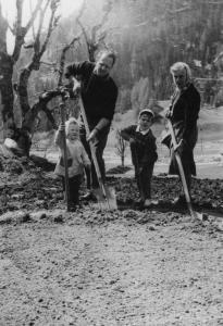 Adulti e bambini che vangano il campo a Valdo