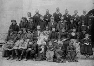 Bambini, giovani e anziani in posa col loro parroco per una foto di gruppo